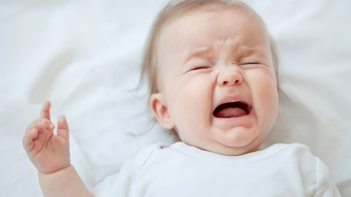 baby crying on bed